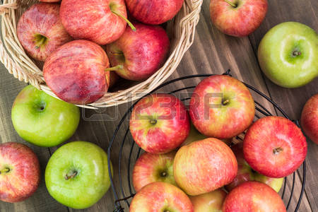 56346499-close-up-of-assorted-ripe-apples-in-a-baskets-and-wooden-background
